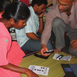 Parikh demonstrates a mobile data-collection system to NGO field staff member
