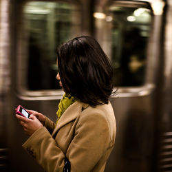 female in subway with cell phone