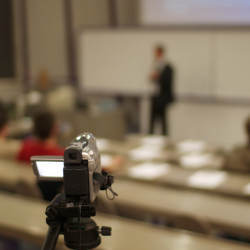 camera pointing to lecturer in classroom