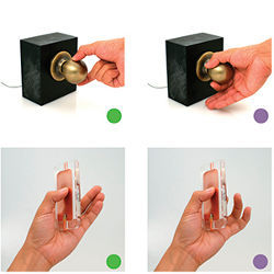 hand grasping a doorknob and fiddling with a handheld device