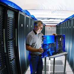 A researcher inspects a supercomputer component.