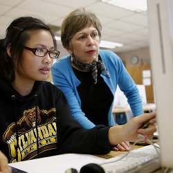Shubha Tuljapurkar, director of educational technology startup Globaloria, an educational tech startup, works with Kayla Pham, 14, during an eighth-grade computer science class at Sylvandale Middle School in San Jose.