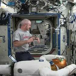 NASA astronaut and International Space Station commander Steve Swanson with Robonaut 2.