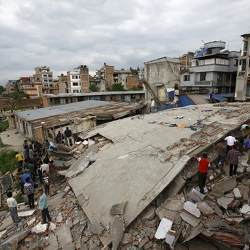 People gather near a collapsed house after a major earthquake in Kathmandu, Nepal, April 26, 2015.