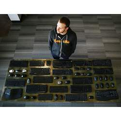 Security researcher Marc Newlin, with wireless peripherals he found vulnerable to a radio keystroke injection attack.