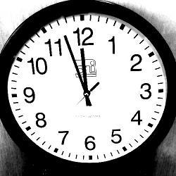 A clock showing the time as three minutes before 12.