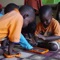 Students in Uganda using a tablet computer.