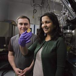 Researchers Jose Pacheco and Meenakshi Singh, who holds an sample qubit structure embedded in silicon.