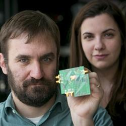 Associate professor Al Molnar and graduate student Hazal Yüksel with a test board with the two-way transceiver chip mounted in the center.