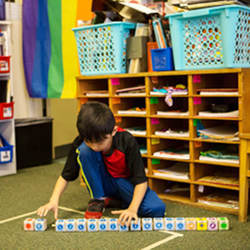 A kindergartner organizes blocks into a sequence of commands.