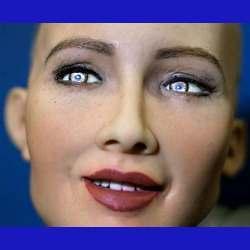 Robot Sophia smiles, bats her eyelids, and tells a joke.