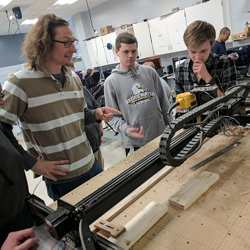 Monticello High School teacher Eric Bredder (left) confers with students using a CNC milling machine.