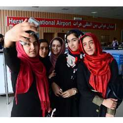 Afghan teens from the Afghanistan Robotic House take photos at Herat International Airport before embarking for the U.S.