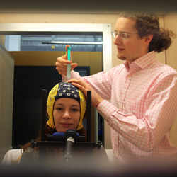 A researcher applies contact gel, to achieve better brain signal transmission quality.