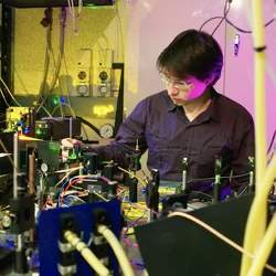 Milos Rancic with the experimental setup used to investigate materials for a telecom-compatible quantum memory.