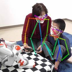 A therapy session augmented with the NAO humanoid robot, showing how facial and limb motions were tracked.