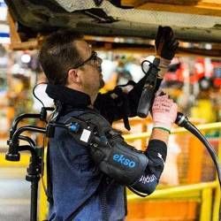 A Ford factory worker wearing the EksoVest exoskeleton.