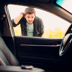 man peering into locked car