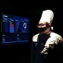 A worker checks a management screen that integrates artificial intelligence, big data management, and smart robot service, in the kitchen of of a hot pot restaurant in Beijing.