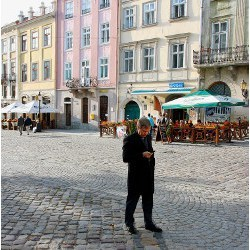 man on cobblestone street examines mobile phone