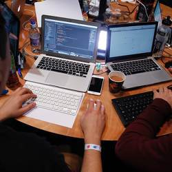 Attendees working on Apple Inc. laptop computers participate in the TechCrunch Disrupt London 2015 Hackathon.