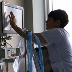 A nurse adjusts settings on a bedside patient monitor.