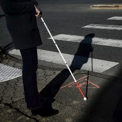 person with white cane in a crosswalk