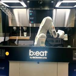 A b;eat robot barista making coffee at a Dal.Komm Coffee franchise.