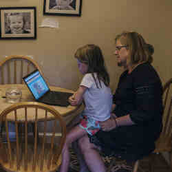 A mother plays educational games on the computer with her daughter.