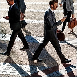 businessmen walking and staring at phones