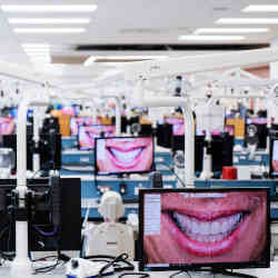 In a dental college classroom, software shows how patients will look after treatment.