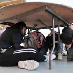 Students participate in an earthquake drill.