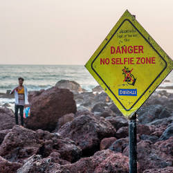 individual near 'Danger No Selfie Zone' sign