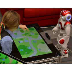 A child interacts with the robot tutor while a teacher provides guidance to the robot