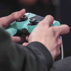 A gamer holds a Playstation 4 controller.