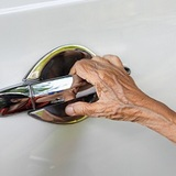 hand of elderly person on car door handle