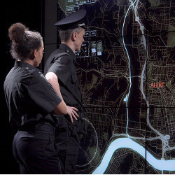 police officers examine wall-sized map display
