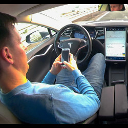man in driver's seat of autonomous vehicle looks at cellphone