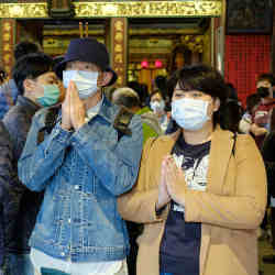 Visitors to a temple in Taipei, Taiwan, wearing surgical masks.