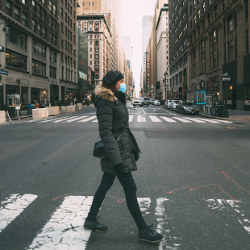 person wearing winter coat and face mask crossing city street