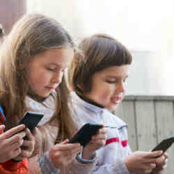 Children playing apps on smartphones.