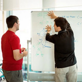 coder at whiteboard explaining his work