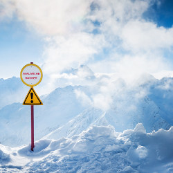 'Avalanche Danger' sign on snowy mountaintop