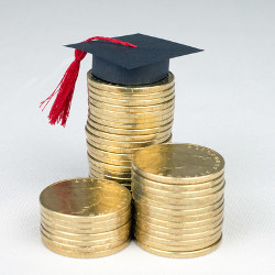 graduation cap and stacks of coins