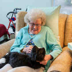 A nursing home resident with a robopet.