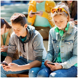 young male and female looking at smartphones