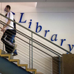 man walking up stairs in library