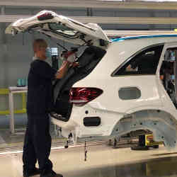 An auto worker assembling a vehicle in a factory operated by Beijing Benz Automotive.