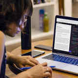 A coding student works remotely on a Codecademy course.